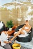 Θεραπεία ποδιών SPA Επεξεργασία προσοχής σώματος γυναικών μασάζ 'Εφαρμογή' του διαφανούς βερνικιού δερμάτων προσοχής Στοκ Εικόνες