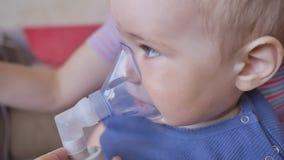 Θεραπεία της ασθένειας πνευμόνων με inhaler Ένα μικρό αγόρι στη μάσκα inhaler Επεξεργασία στο σπίτι φιλμ μικρού μήκους