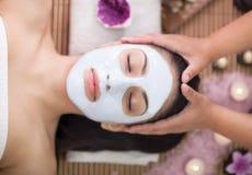 Θεραπεία SPA για τη νέα γυναίκα που έχει την του προσώπου μάσκα στο σαλόνι ομορφιάς Στοκ Φωτογραφίες