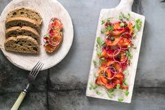 Θεραπευμένος σολομός με το κρεμμύδι, τα πράσινα και το ψωμί, Σκανδιναβικό πιάτο στοκ φωτογραφίες