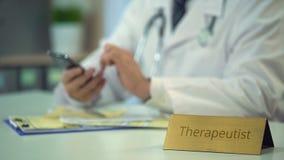 Θεραπευτής που χρησιμοποιεί το smartphone στην εργασία, που έρχεται σε επαφή με τον ασθενή για να ενημερώσει τη διάγνωση απόθεμα βίντεο