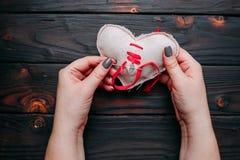 Θεραπεύοντας σπασμένη καρδιά Χέρια που ράβουν μια καρδιά υφάσματος με μια βελόνα Στοκ Εικόνα
