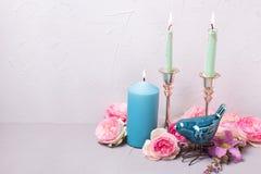 Θερινά λουλούδια, διακοσμητικό πουλί και καίγοντας κεριά στο γκρίζο te Στοκ φωτογραφία με δικαίωμα ελεύθερης χρήσης