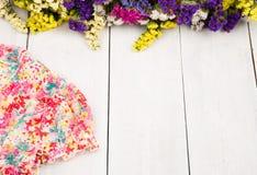 θερινές γυναίκες που τίθενται με το φόρεμα και τα ζωηρόχρωμα λουλούδια άσπρο σε ξύλινο Στοκ Εικόνες