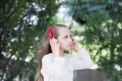 Θερινές διακοπές και διασκέδαση Το μικρό κορίτσι ακούει μουσική στο θερινό πάρκο Το παιδί απολαμβάνει τη μουσική στα ακουστικά υπ Στοκ Εικόνες