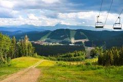 Θερινή άποψη του Καρπάθιου τοπίου βουνών σε Bukovel, Ουκρανία Πράσινα δάση, λόφοι, χλοώδεις λιβάδια και μπλε ουρανός Στοκ Εικόνα