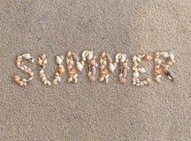Θερινή λέξη που γίνεται από τα διάφορα κοχύλια θάλασσας στο backgro άμμου παραλιών Στοκ Εικόνες