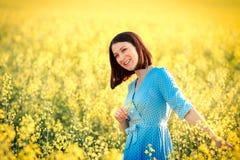 Θερινή διάθεση Ελκυστικό κορίτσι στο μπλε φόρεμα στον κίτρινο τομέα Smil Στοκ Εικόνες