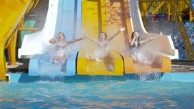 Θερινή διασκέδαση στο πάρκο νερού, τα γενναία κορίτσια που γλιστρούν κάτω στα waterslides και την κατάδυση στη λίμνη με το ράντισ απόθεμα βίντεο