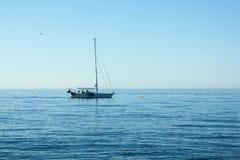 Θερινή μπλε ημέρα στην ακτή με την πλέοντας βάρκα Στοκ εικόνα με δικαίωμα ελεύθερης χρήσης