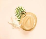 Θερινή μόδα, θερινή εξάρτηση στο υπόβαθρο κρέμας Θαλασσινό κοχύλι, ξύλινα βραχιόλι και καπέλο αχύρου Επίπεδος βάλτε, τοπ άποψη Στοκ εικόνα με δικαίωμα ελεύθερης χρήσης