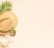 Θερινή μόδα, θερινή εξάρτηση στο υπόβαθρο κρέμας Θαλασσινό κοχύλι, ξύλινα βραχιόλι και καπέλο αχύρου Επίπεδος βάλτε, τοπ άποψη Στοκ Φωτογραφίες