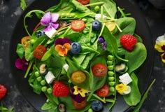 Θερινή σαλάτα με τα εδώδιμα λουλούδια, το σπανάκι, τα βακκίνια, το σμέουρο, τα γλυκά μπιζέλια, τις ντομάτες κερασιών και το τυρί  Στοκ φωτογραφίες με δικαίωμα ελεύθερης χρήσης