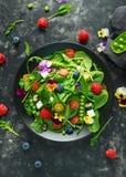 Θερινή σαλάτα με τα εδώδιμα λουλούδια, το σπανάκι, τα βακκίνια, το σμέουρο, τα γλυκά μπιζέλια, τις ντομάτες κερασιών και το τυρί  Στοκ εικόνες με δικαίωμα ελεύθερης χρήσης