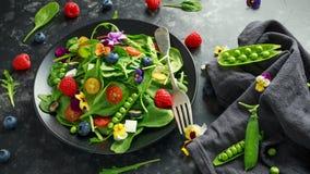 Θερινή σαλάτα με τα εδώδιμα λουλούδια, το σπανάκι, τα βακκίνια, το σμέουρο, τα γλυκά μπιζέλια, τις ντομάτες κερασιών και το τυρί  Στοκ Φωτογραφία