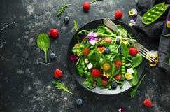 Θερινή σαλάτα με τα εδώδιμα λουλούδια, το σπανάκι, τα βακκίνια, το σμέουρο, τα γλυκά μπιζέλια, τις ντομάτες κερασιών και το τυρί  Στοκ Φωτογραφίες