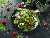 Θερινή σαλάτα με τα εδώδιμα λουλούδια, το σπανάκι, τα βακκίνια, το σμέουρο, τα γλυκά μπιζέλια, τις ντομάτες κερασιών και το τυρί  Στοκ Εικόνες