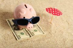 Θερινή piggy τράπεζα που στέκεται στην πετσέτα από το χαρτονόμισμα εκατό δολάρια με τα γυαλιά ηλίου στην παραλία και κόκκινο paras