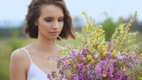 Θερινός ανθίζοντας τομέας και ένα όμορφο κορίτσι άσπρα sundress απόθεμα βίντεο