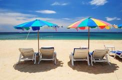 Θερινός παράδεισος με την άσπρη καρέκλα και τη ζωηρόχρωμη ομπρέλα Στοκ Φωτογραφίες