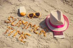 Θερινός χρόνος επιγραφής, εξαρτήματα για την ηλιοθεραπεία και διαβατήριο με το δολάριο νομισμάτων στην άμμο στην παραλία, θερινός Στοκ φωτογραφία με δικαίωμα ελεύθερης χρήσης
