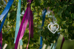 Θερινό δέντρο στο μπλε και ιώδες άνθος με τη γαμήλια διακόσμηση - καρδιές κορδελλών Στοκ Εικόνες