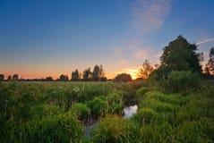 Θερινό ηλιοβασίλεμα γύρω από τον τομέα και τον ποταμό Στοκ Εικόνες