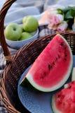 Θερινό πικ-νίκ: καλάθι με το καρπούζι, στα μήλα υποβάθρου και τα τριαντάφυλλα στοκ εικόνα με δικαίωμα ελεύθερης χρήσης