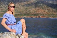 Θερινό πορτρέτο του όμορφου κοριτσιού στα γυαλιά ηλίου που κάθεται κοντά στη θάλασσα και τα βουνά στοκ φωτογραφία με δικαίωμα ελεύθερης χρήσης