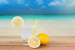 Θερινό ποτό λεμονάδας πάγου, ωκεάνια παραλία θαμπάδων στο υπόβαθρο Στοκ εικόνες με δικαίωμα ελεύθερης χρήσης