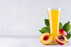 Θερινό ποτό - χυμός ροδάκινων και κόκκινα ώριμα νεκταρίνια με τα φύλλα και σαρκώδης φέτα στο μαλακό ελαφρύ άσπρο ξύλινο υπόβαθρο στοκ εικόνα με δικαίωμα ελεύθερης χρήσης