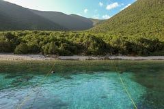 Θερινό πρωί η γραφική φύση της παραλίας ANTISAMOS με το τυρκουάζ κρύσταλλο - καθαρίστε το νερό, άσπρα χαλίκια, πράσινα δέντρα Kef στοκ εικόνα