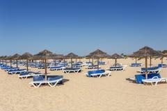 Θερινό πρωί στην παραλία του Αλγκάρβε Sunbeds στην άμμο Στοκ φωτογραφία με δικαίωμα ελεύθερης χρήσης