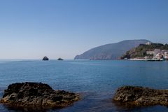 Θερινό τοπίο, βουνό, απότομος βράχος, θάλασσα και καθαρός μπλε ουρανός ενάντια ανασκόπησης μπλε σύννεφων πεδίων άσπρο σε wispy ου Στοκ εικόνα με δικαίωμα ελεύθερης χρήσης
