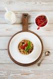 Θερινό υγιές πρόγευμα του granola, muesli με την κανάτα γάλακτος με το ντεκόρ κόκκινων σταφίδων στον ελαφρύ ξύλινο πίνακα Στοκ Εικόνες