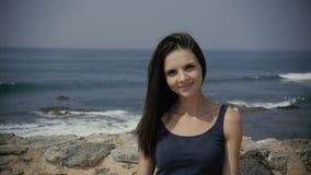 Θερινό υπαίθριο πανέμορφο προκλητικό κορίτσι μόδας με τη σκοτεινή τοποθέτηση τρίχας στην παραλία, όμορφος τουρίστας γυναικών φιλμ μικρού μήκους