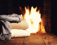 Θερμά μάλλινα πράγματα κοντά στην εστία στον ξύλινο πίνακα Στοκ φωτογραφία με δικαίωμα ελεύθερης χρήσης