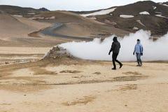 Θερμά ντυμένοι άνδρας και γυναίκα που περπατούν δίπλα στην ατμίδα στο πάρκο Hverir, Ισλανδία Στοκ εικόνα με δικαίωμα ελεύθερης χρήσης