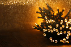 Θερμά χρυσά φω'τα γιρλαντών Χριστουγέννων στο ξύλινο αγροτικό υπόβαθρο Φιλτραρισμένη εικόνα Στοκ Φωτογραφία