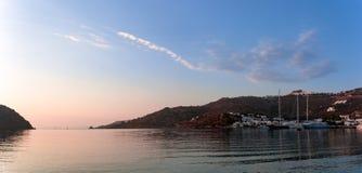 Θερμά χρώματα αυγής πέρα από το λιμάνι του νησιού Patmos, Dodecanese, Ελλάδα Στοκ Εικόνα