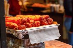 Θερμά churros κάτω από έναν λαμπτήρα θερμότητας στην επίδειξη στην αγορά του Κάμντεν στοκ φωτογραφίες
