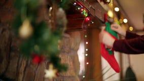 Θερμή άνετη εστία πετρών που διακοσμείται για τα Χριστούγεννα με το στεφάνι, γυναικείες κάλτσες, φω'τα γιρλαντών Mantelpiece με τ απόθεμα βίντεο