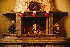 Θερμή άνετη εστία που διακοσμείται για τα Χριστούγεννα με το πραγματικό ξύλινο burni στοκ εικόνα