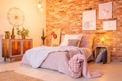 Θερμή κρεβατοκάμαρα με το τουβλότοιχο στοκ φωτογραφία
