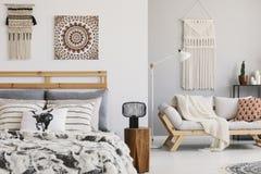 Θερμή κρεβατοκάμαρα ethno με τα διαμορφωμένα μαξιλάρια στο κρεβάτι και τον καναπέ και macrame στον τοίχο στοκ εικόνες