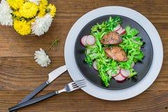Θερμή σαλάτα με το συκώτι κοτόπουλου, το arugula και το ραδίκι με τη σάλτσα στο μαύρο πιάτο αγροτικός ξύλινος ανασκόπησης Εκλεκτι Στοκ εικόνα με δικαίωμα ελεύθερης χρήσης