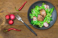 Θερμή σαλάτα με το συκώτι κοτόπουλου, το arugula και το ραδίκι με τη σάλτσα στο μαύρο πιάτο αγροτικός ξύλινος ανασκόπησης Εκλεκτι Στοκ Φωτογραφίες