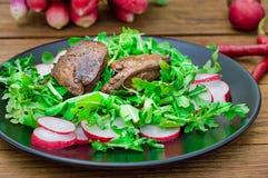 Θερμή σαλάτα με το συκώτι κοτόπουλου, το arugula και το ραδίκι με τη σάλτσα στο μαύρο πιάτο αγροτικός ξύλινος ανασκόπησης Εκλεκτι Στοκ φωτογραφίες με δικαίωμα ελεύθερης χρήσης