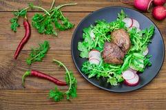 Θερμή σαλάτα με το συκώτι κοτόπουλου, το arugula και το ραδίκι με τη σάλτσα στο μαύρο πιάτο αγροτικός ξύλινος ανασκόπησης Εκλεκτι Στοκ Εικόνες