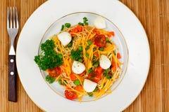 Θερμή σαλάτα των νουντλς, κολοκύθα, καρότα, μπιζέλια με την ντομάτα κερασιών Στοκ Φωτογραφίες